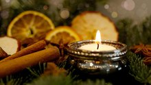 Christmas candle, cinnamon sticks, orange and apple slices amid pine branches